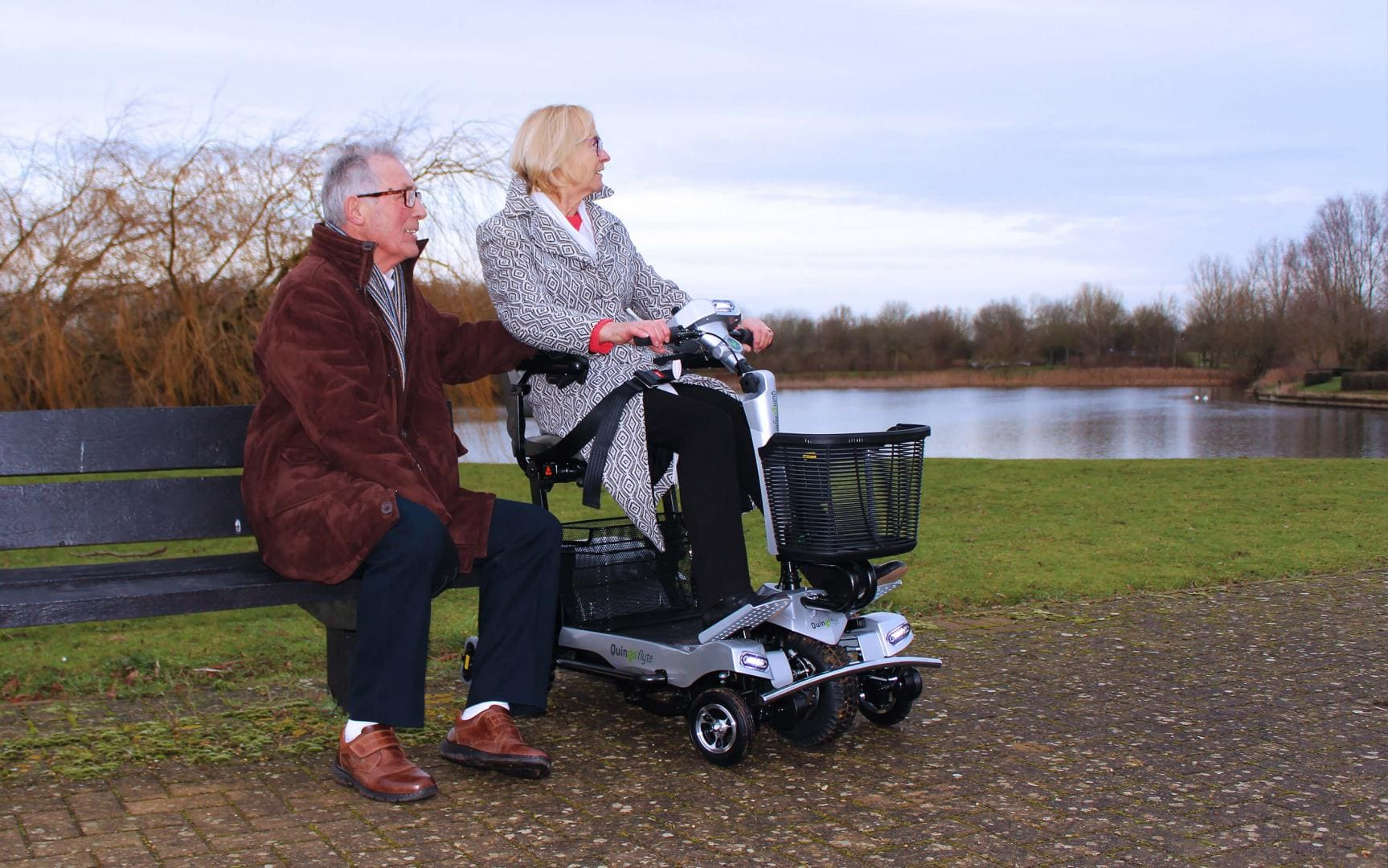 A Lady sitting on a Quingo Flyte electric scooter next to a man in a park