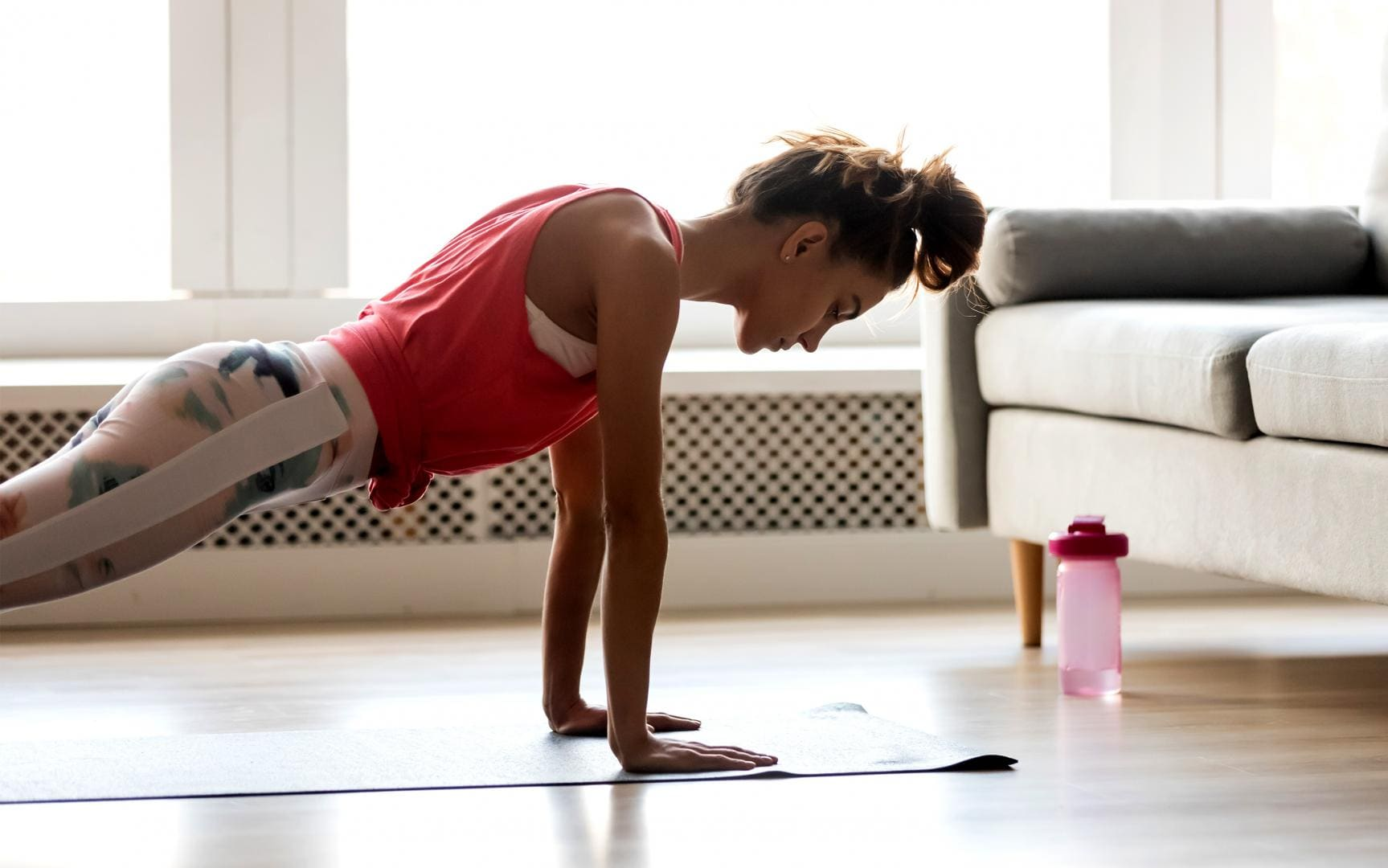 Woman holding a plank position, whilst she exercises on the floor
