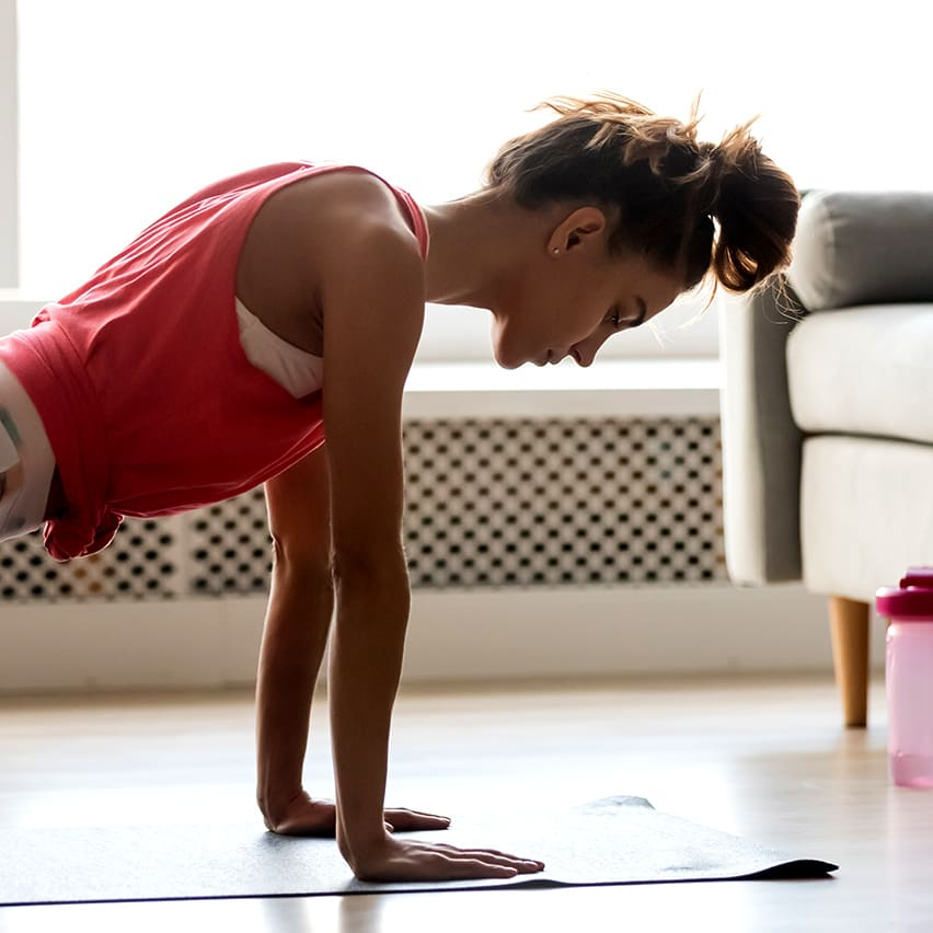 Image of woman folding a plank position, exercising on the floor