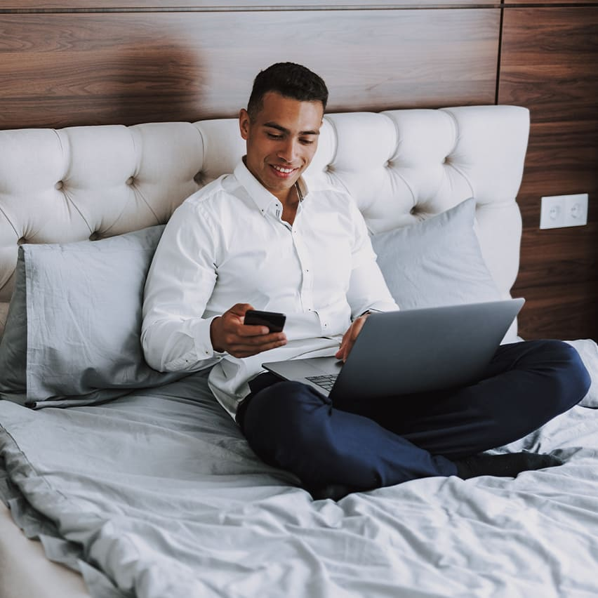 Man sitting on a Guestkey hotel bed on his phone and laptop